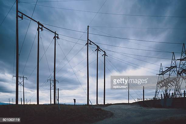 Man stands on horizon beneath electrical lines along gravel road