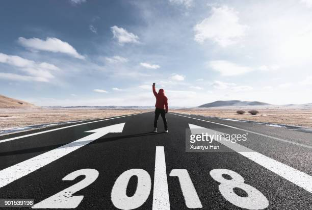 man Stands On Long Road With 2018 Painted On It