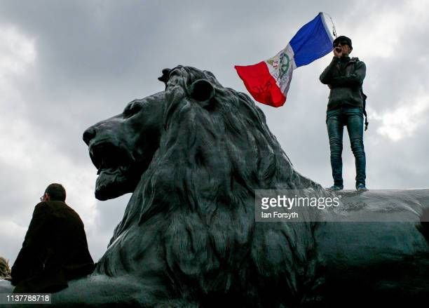 A man stands on one of the lions in Trafalgar Square as thousands of demonstrators take to the streets of London during the People's Vote March on...