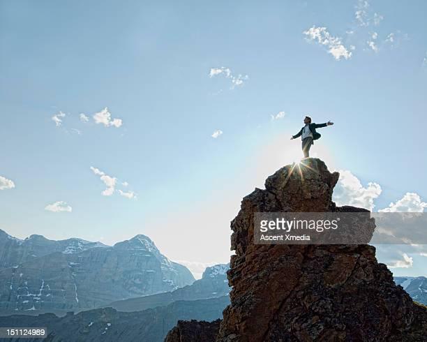 man stands on peak, arms outstretched. - sucesso - fotografias e filmes do acervo