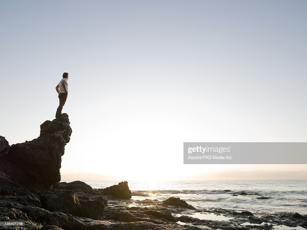 Man stands on rock above sea, looks out : Stock Photo