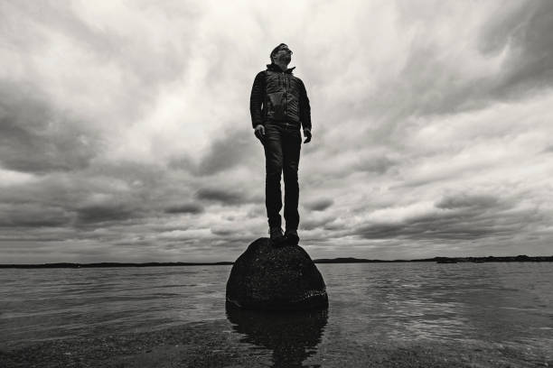 man stands on rock in middle of lake with storm clouds looming