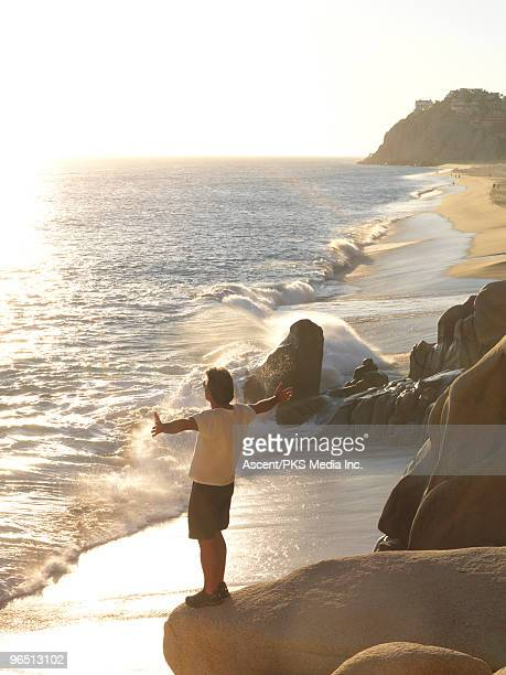 Man stands on rock overlooking sea, arms outstretc
