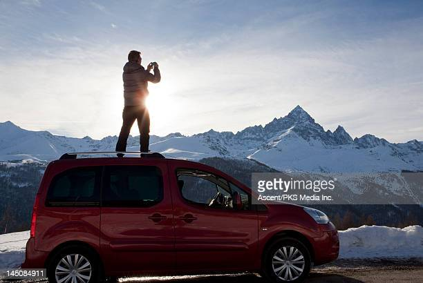 Man stands on roof of vehicle, takes pic of mtns