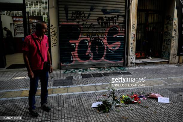A man stands on September 24 2018 in front of flowers outside a jewelry shop were a man was beaten to death in central Athens Athens prosecutor's...