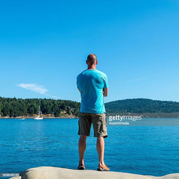 Man stands on shoreline rocks, looks out to sea