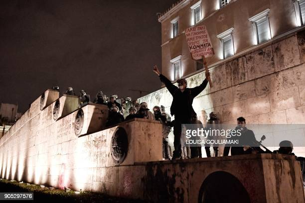 TOPSHOT A man stands on stairs leading to the Greek parliament in Athens on January 15 during a parliamentary vote on controversial reforms demanded...