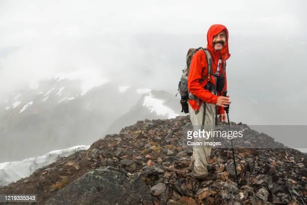 man stands on summit of cooper mountain, kenai peninsula, alaska - kenai mountains stock pictures, royalty-free photos & images