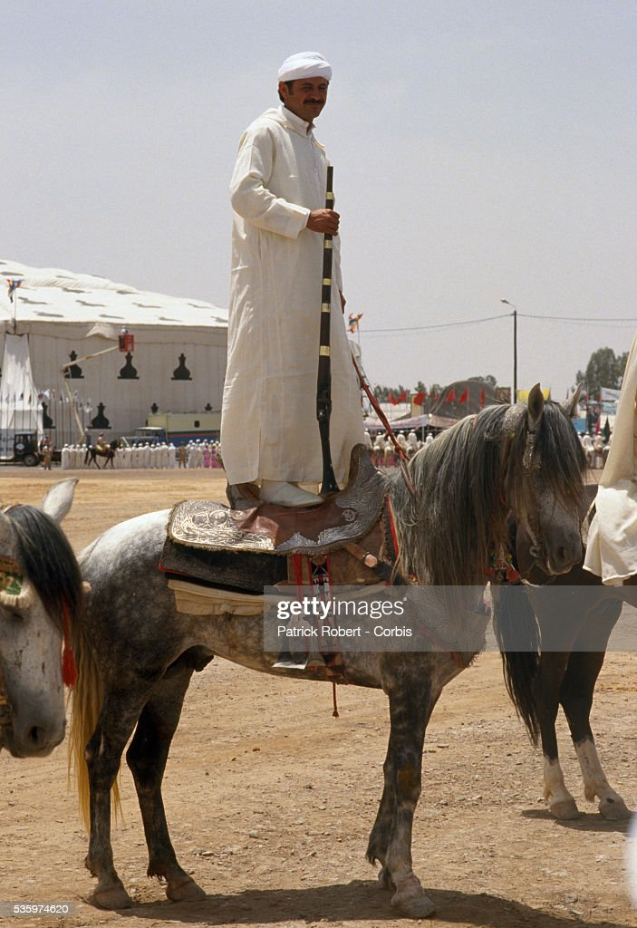 A man stands on the back of his horse at a celebration for the wedding of Princess Lalla Asmaa, daughter of Hassan II, King of Morocco.