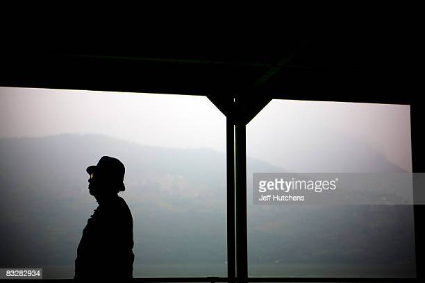 A man stands on the docks of the Yangtze River on part of the river responsible for the forced relocation of residents whose homes are being...
