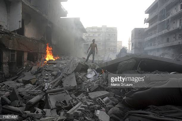 Man stands on the remains of a building as civilians and rescue teams try to extinguish fires and search for survivors after Israeli war planes...