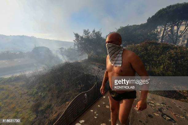 Man stands on the roof of his house and look towards smoke on the horizon during a vast fire that threatened the inhabited areas between Naples and...