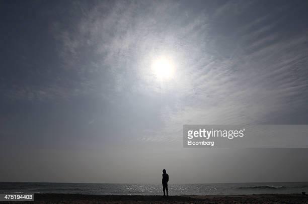A man stands on the seashore near the Chubu Electric Power Co's Hamaoka nuclear power station unseen in Omaezaki Shizuoka prefecture Japan on...