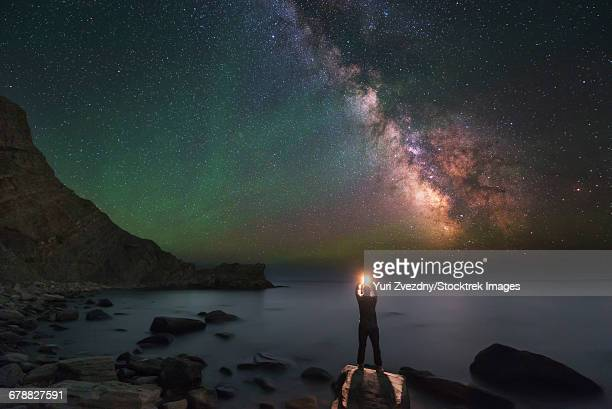 A man stands on the shore of the Black Sea at night under Milky Way and green airglow.