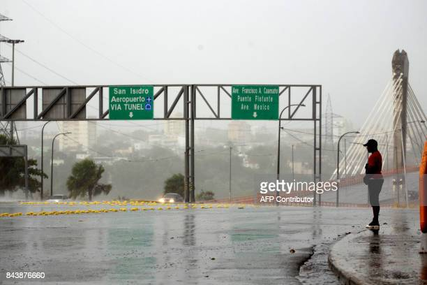 TOPSHOT A man stands on the sidewalk in the rain in the La Cienaga neighborhood on September 7 as Hurricane Irma approaches Irma was packing maximum...