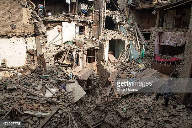 A man stands on top of debris from collapsed buildings on April 26 2015 in Bhaktapur Nepal A major 78 earthquake hit Kathmandu midday on Saturday and...