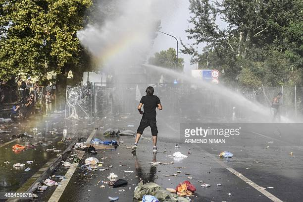 A man stands opposite Hungarian riot police using water cannon to push back refugees at the Hungarian border with Serbia near the town of Horgos on...