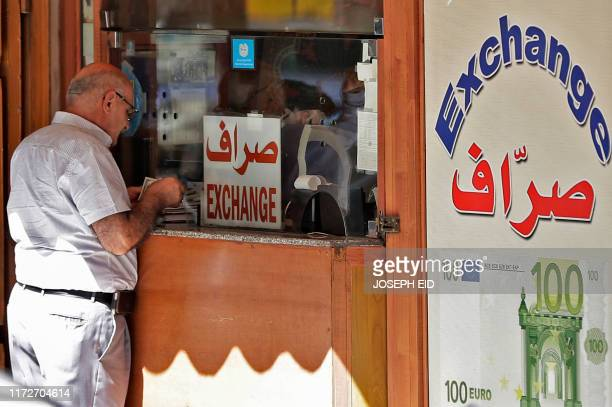 A man stands outside a currency exchange company booth in the Lebanese capital Beirut on October 1 2019 Lebanon's central bank announced Monday...