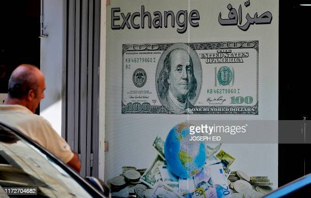 A man stands outside a currency exchange company in the Lebanese capital Beirut on October 1 2019 Lebanon's central bank announced Monday adopting a...