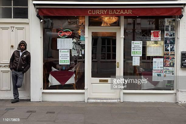 A man stands outside a curry house on Brick Lane which is synonymous with curry restaurants on March 16 2011 in London England From April 2011 the...