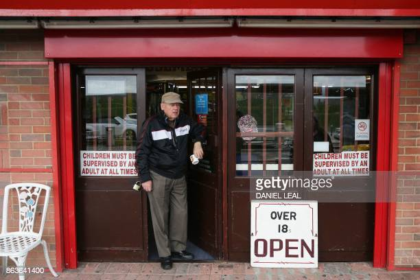 A man stands outside an arcade game shop on Canvey Island Essex on October 20 2017 A small island community in the Thames Estuary that voted...