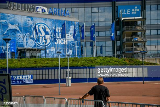 Man stands outside the arena and the training ground pof the Bundesliga football club Schalke 04 in Gelsenkirchen, western Germany, where fans...