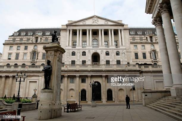 A man stands outside the Royal Exchange in front of the Bank of England in a neardeserted City of London midmorning on Monday March 30 as life in...
