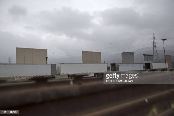A man stands over a trailer covering the US prototypes of the border wall with Mexico as seen from Tijuana Baja California state Mexico on March 10...