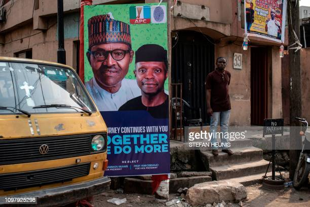 A man stands past a big poster of Nigeria's current President Mohammadu Buhari in Lagos on February 11 2019 Nigerians will participate in the...