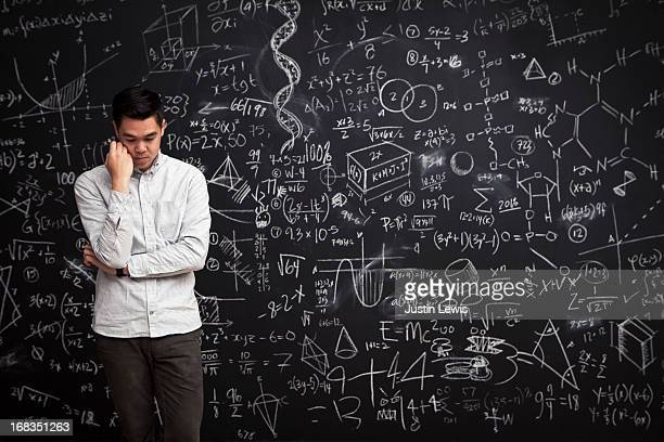 Man stands thinking in front of math chalkboard