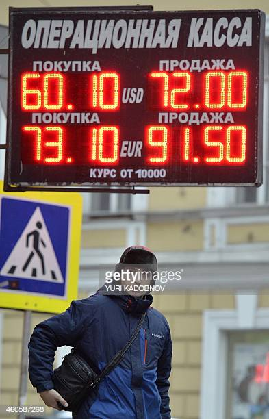 A man stands under a board listing foreign currency rates against the Russian ruble outside an exchange office in central Moscow on December 17 2014...