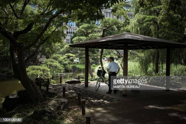 A man stands under a shelter in a park in Tokyo on July 23 as Japan suffers from a heatwave Japan's severe heatwave killed at least 15 people and...