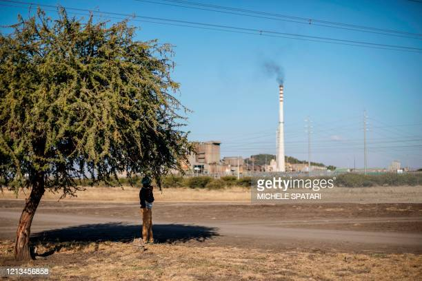 A man stands under a tree next to Wonderkop in Marikana near Rustenburg on May 15 with the SibanyeStillwater platinum mine in the background The...