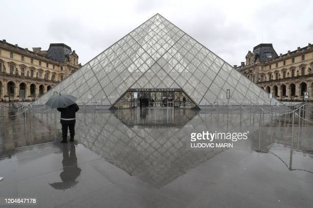 TOPSHOT A man stands under an umbrella looking at the deserted courtyard outside the Louvre Pyramid the main entrance to the museum which was once a...