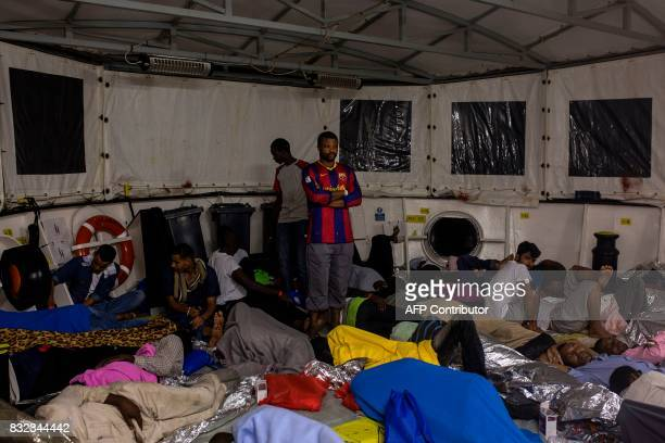 A man stands uo as migrants sleep on the deck of the Aquarius rescue ship run by NGO SOS Mediterranee and Medecins Sans Frontieres after their...