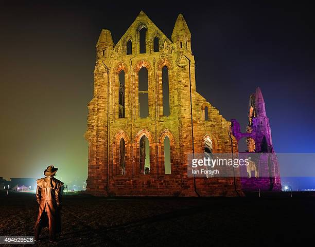 Man stands watching as a spectacular light display illuminates the historic Whitby Abbey on October 27, 2015 in Whitby, England. The famous...