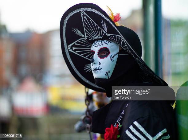 A man stands wearing a decorative mask during Whitby goth Weekend on October 27 2018 in Whitby England The Whitby goth weekend began in 1994 and...