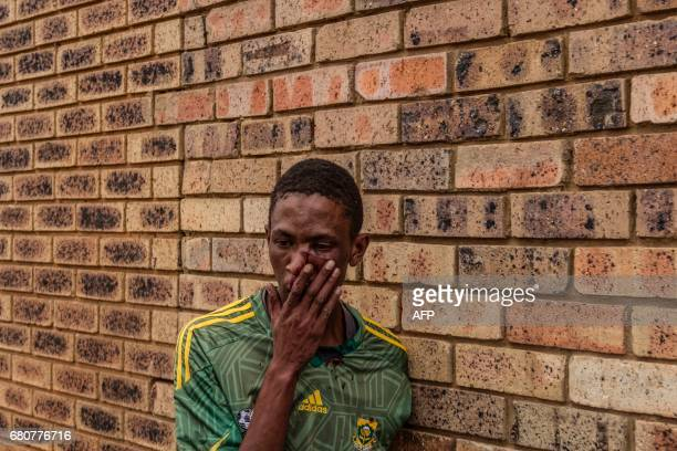 A man stands with a bloodied face after he was assaulted by protestors in Ennerdale a suburb in the south of Johannesburg who accused him of stealing...