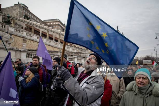 A man stands with an EU flag during speeches at a demonstration against recent legislative measures introduced by Hungarian Prime Minister Viktor...