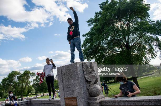 A man stands with his fist raised on the spot where a statue of Christopher Columbus which was toppled by protesters stood on the grounds of the...