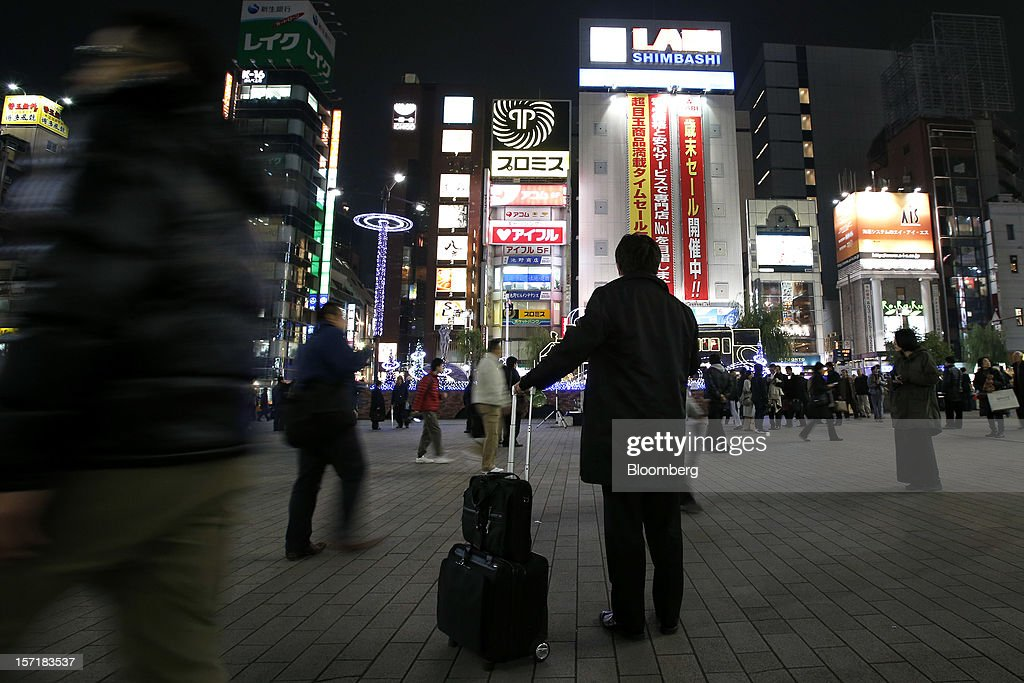 A man stands with his luggage as people walk by in Tokyo, Japan, on Thursday, Nov. 29, 2012. Japan's cabinet approved a second round of fiscal stimulus worth 880 billion yen ($10.7 billion) using budget reserves as Prime Minister Yoshihiko Noda attempts to boost the economy before elections on Dec. 16. Photographer: Kiyoshi Ota/Bloomberg via Getty Images
