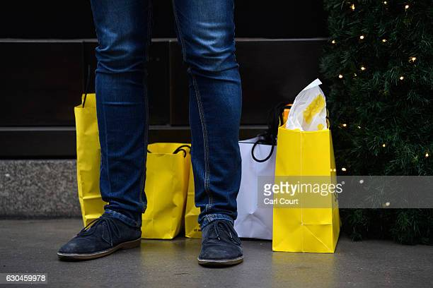 A man stands with his shopping outside a store on Oxford Street on December 23 2016 in London England Shoppers are continuing to spend as stores...