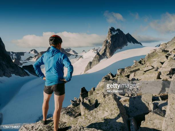 man stands with out his pants on while standing on side of mountain looking out at glaciers and rocky mountains - junge in unterhose stock-fotos und bilder