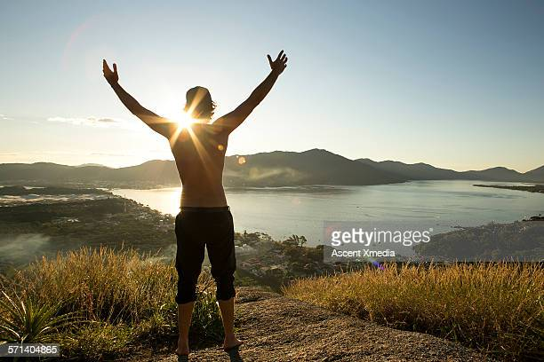 Man stands with raised arms above lagoon, sunrise
