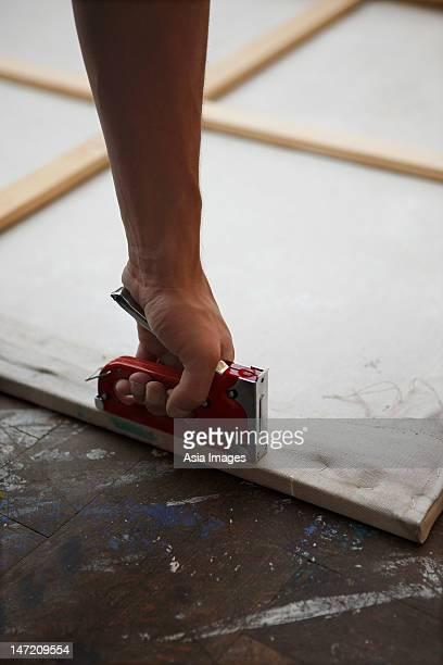 man stapling canvas