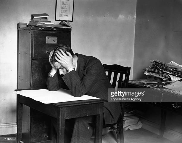 Man staring at blank sheet of paper with his head in his hands.