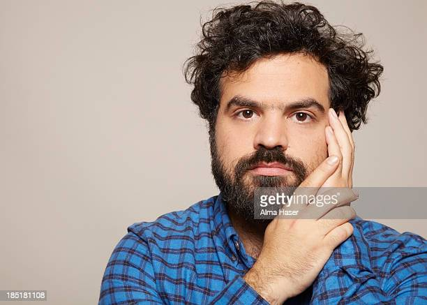 Man staring at camera with hands placed on face