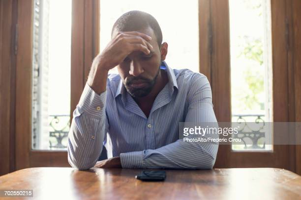 Man staring at cell phone with look of disappointment