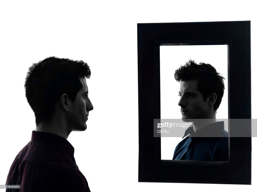 Man staring at his own reflection in mirror : Stock Photo