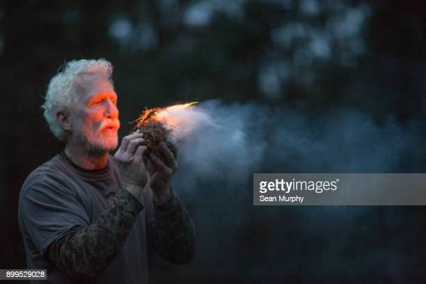 man starting fire light - camouflage clothing stock pictures, royalty-free photos & images